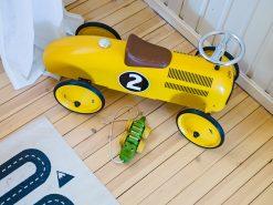 Boligfoto, detaljebilde av gul lekebil på tregulv