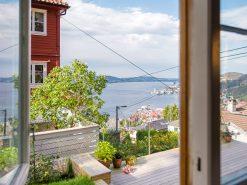 Utsiktsbilde over hage og Byfjorden, sett ut av stuevindu