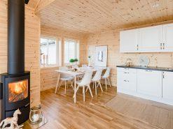 Interiørfoto av nyoppført hytte, peis, spisestue og kjøkken, åpen planløsning, eiendomsfoto