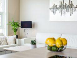Stue, detaljbilde av sofagruppe, uskarp platetopp og skål med sitron i forgrunn