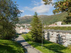 Eksteriørfoto av liten boligblokk på Landås, Ulriken i bakgrunnen