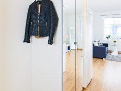 Entré med garderobeskap, stue i bakgrunn, boligfoto