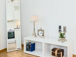 Detaljfoto fra stue, kjøkkeninnretning kan sees i høyt speil som står på gulvet. Boligfoto
