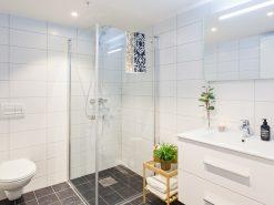 Interiør, helfliset baderom med vegghengt toalett, dusjhjørne, servant og speil