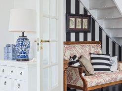 Interiørfoto fra enebolig, del av stue, entré med trapp opp til andre etasje, detaljbilde