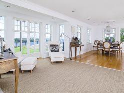 Interiørfoto fra enebolig, stue og spisestue, utsikt mot hage og fjord
