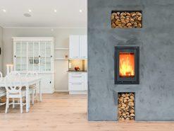 Spisestue, del av kjøkken og betongvegg med vedovn, boligfoto