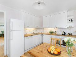 Interiørfoto fra rekkehus, kjøkken og stue i bakgrunnen